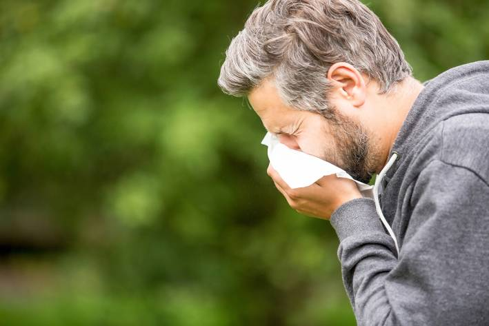 a middle-aged man sneezing into a tissue
