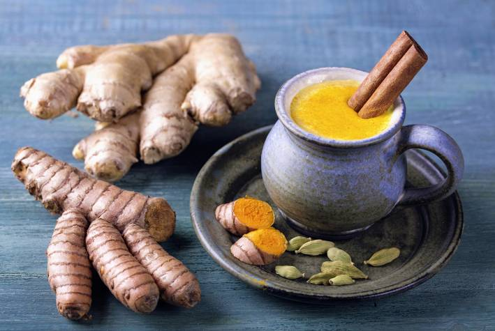 A mug of Golden Milk with turmeric and ginger root beside it.