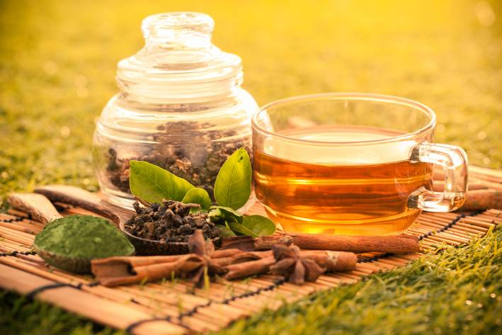 Brewed green tea in a glass cup on a bamboo placemat with dried green tea in a jar next to it outdoors on the grass.