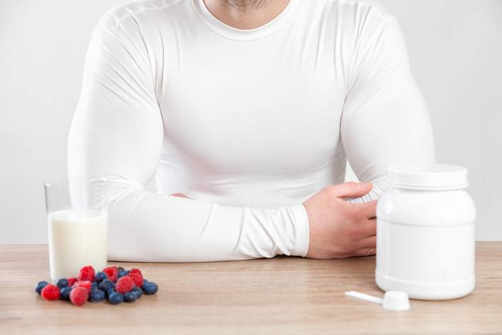 A muscular man at a table with fruits and supplements