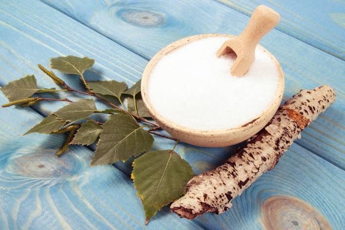 Birch sugar on blue wooden background.
