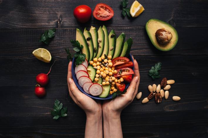 Hands holding healthy salad with chickpea and vegetables.