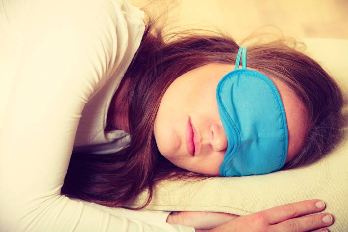 Portrait of brunette woman sleeping in blue eye mask