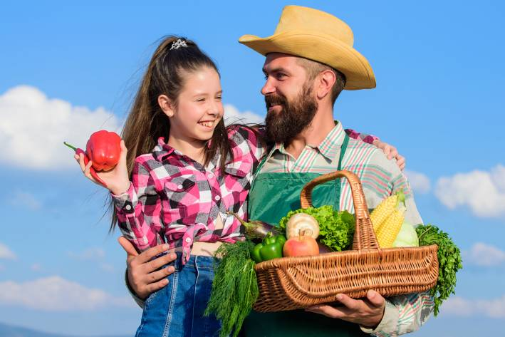 a farmer and his daughter with an organic harvest