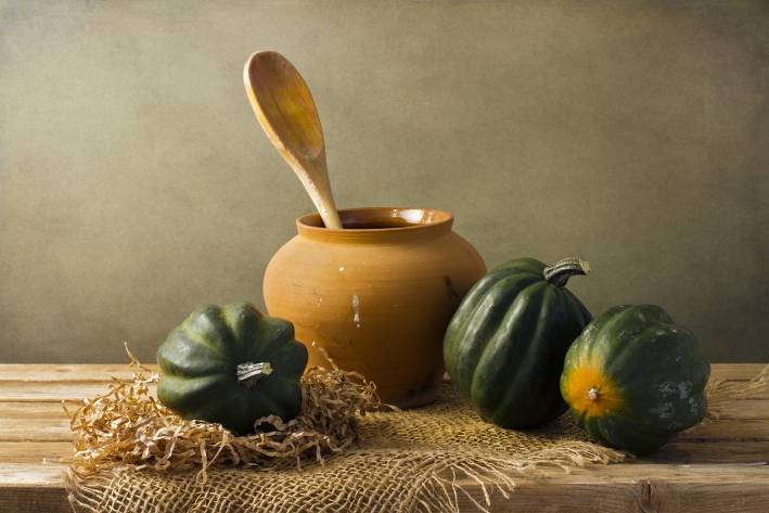 Whole acorn squash on a rustic table next to an earthen vase with a wooden spoon i it.