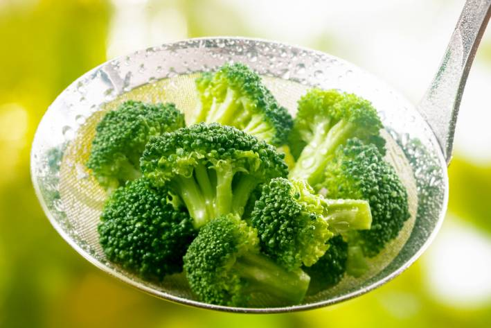 Steamed broccoli in a stainless steel ladle.