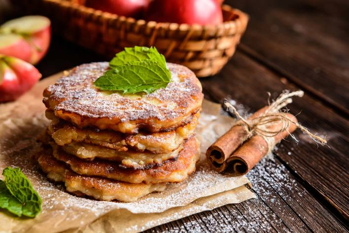 Apple Jack Pancakes stacked on a piece of parchment paper sprinkled with powdered sugar.