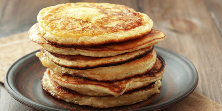 A stack of pancakes on a grey pottery plate placed on a wooden table.