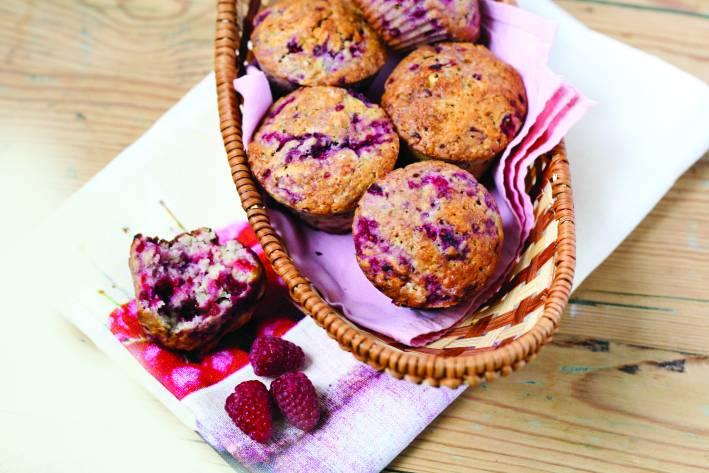 Raspberry muffins in a basket, placed on a white cloth alongside a broken muffin and raspberries.