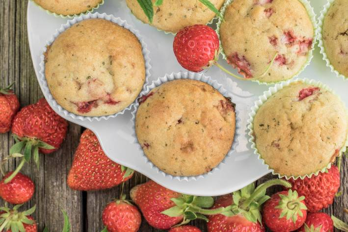 Top view on a strawberry muffins on white plate on a old wooden board