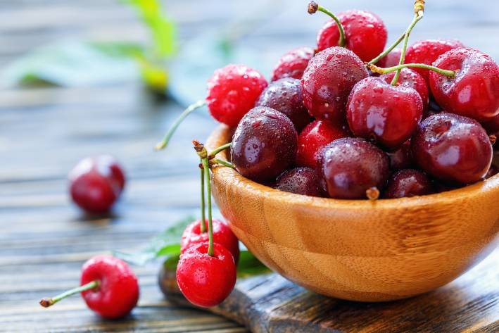 Red sweet cherries in a wooden bowl.