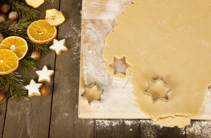 Christmas cookies in the shape of stars are gouged, beside decoration.