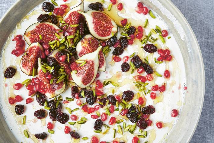 Greek Yogurt Panna Cotta with Pistachios, Pomegranate and Cranberries in a white earthen bowl. Top view.