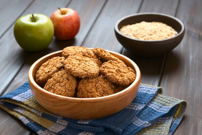Apple Pie Cookies in wooden bowl with apples and oatmeal in the background.
