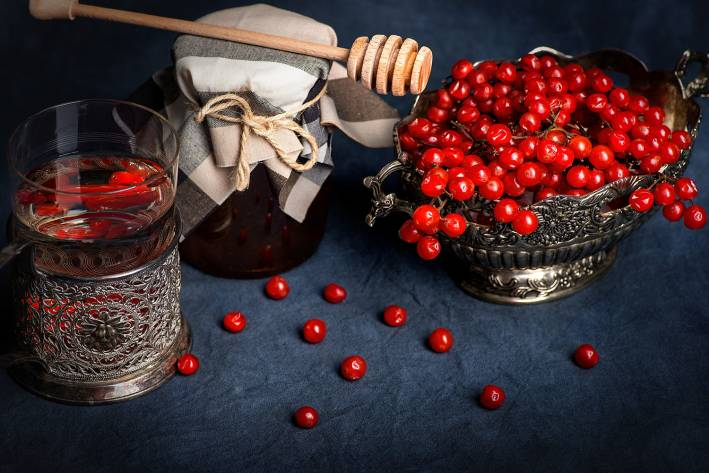Glass in a silver coaster, a vase with medical berries and bank of honey on a dark background