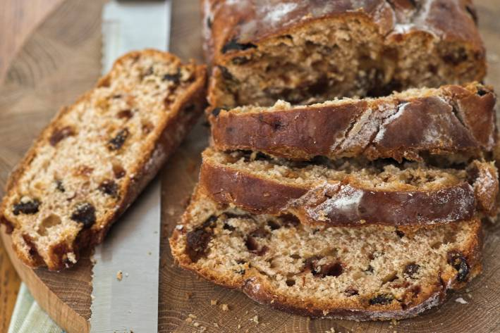 Walnut & Raisin Loaf sliced on a round wooden cutting with bread knife.