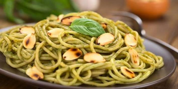 Dish of whole grain pasta, pesto and slivered almonds.