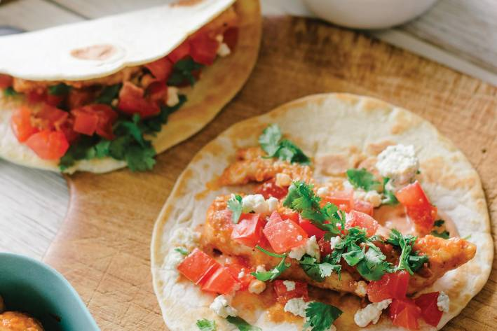Buffalo Chicken Tacos prepared and ready to eat on a cutting board
