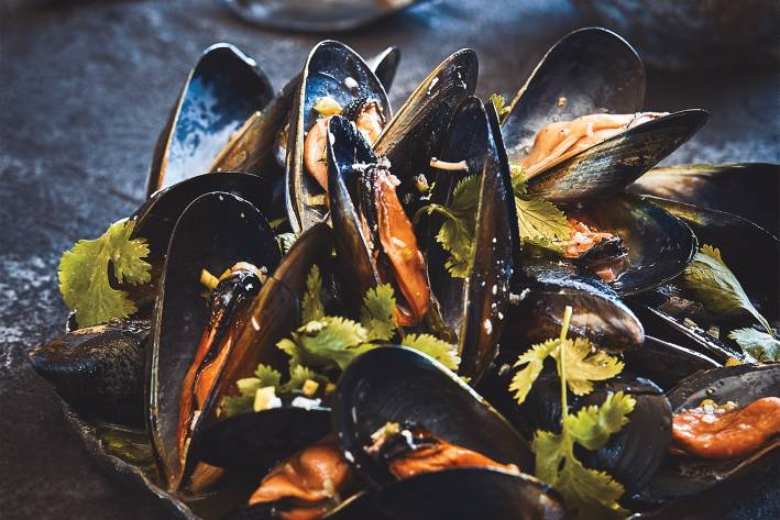 Grilled mussels served on a dark platter