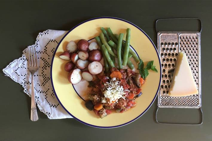 a plate of ground turkey cooked with vegetables, with potatoes and green beans