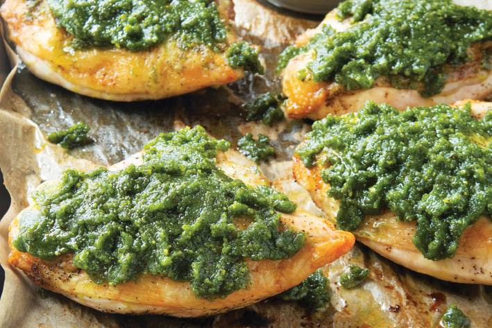 Pistachio Pesto Chicken on a baking sheet with parchment paper.