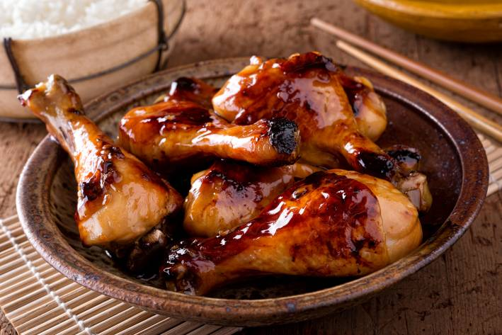 Sticky chicken on a plate ready sprinkle with scallions and serve.