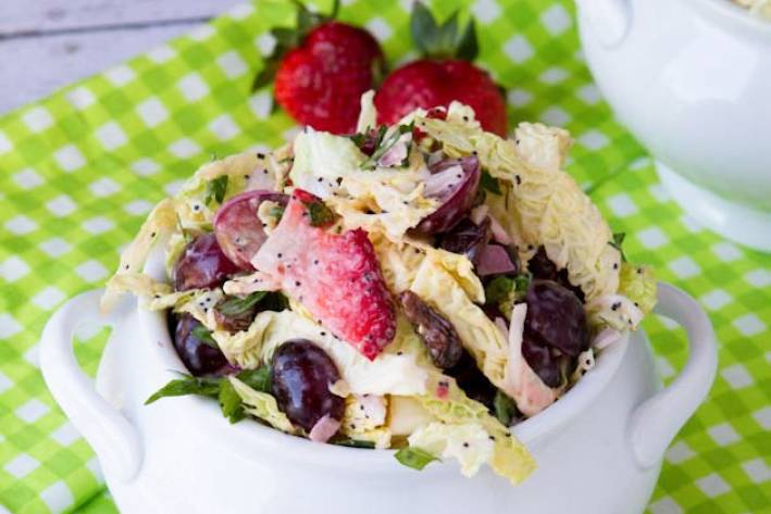 a dish of coleslaw with berries and seeds