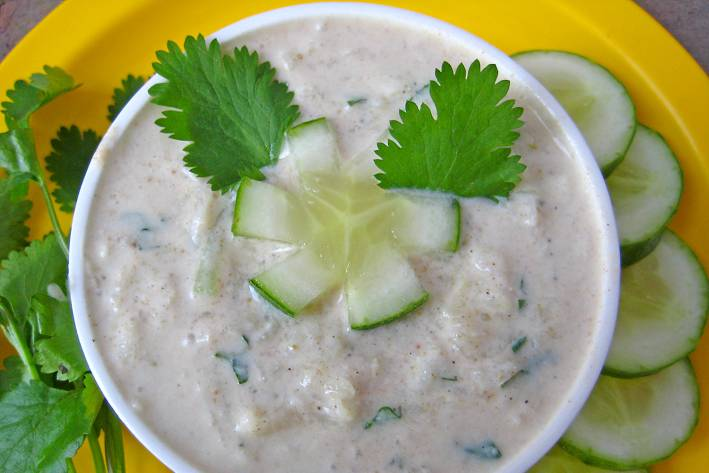 a bowl of Indian spiced yogurt with cucumber