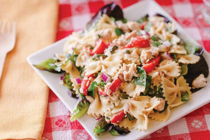 a plate of pasta with tuna and vegetables