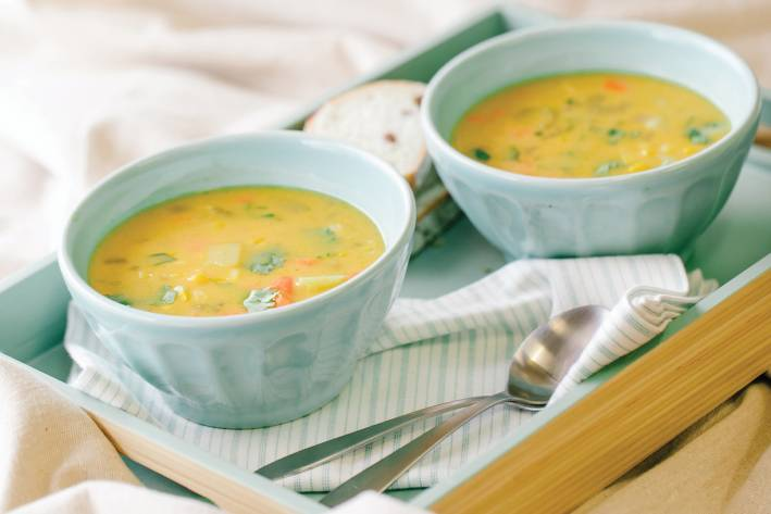 Two light blue bowls of coconut corn chowder on a bamboo serving tray.
