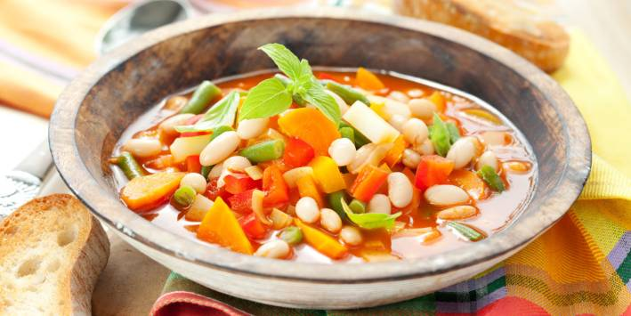 A hot bowl of soup with vegetables and pasta.