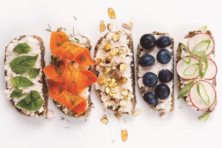 Almond Ricotta on five slices of bread with different toppings in a row.