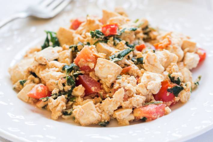 a plate of scrambled tofu with greens and tomatoes