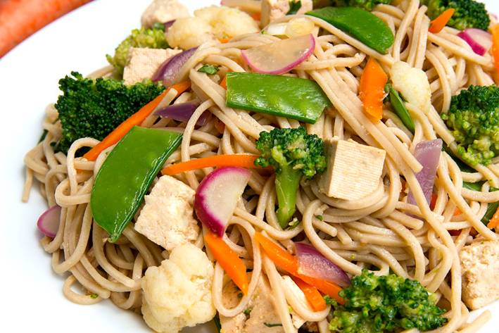 a plate of soba noodles with vegetables and tofu