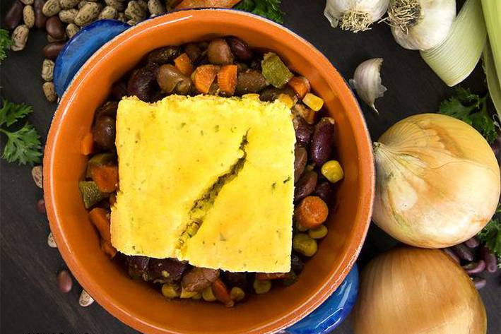 cornbread on top of a bowl of vegetarian chili
