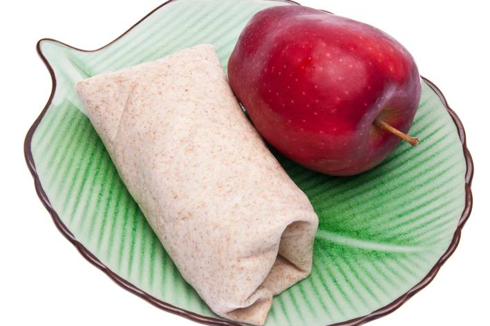 a wrap on a leafy green plate next to an apple