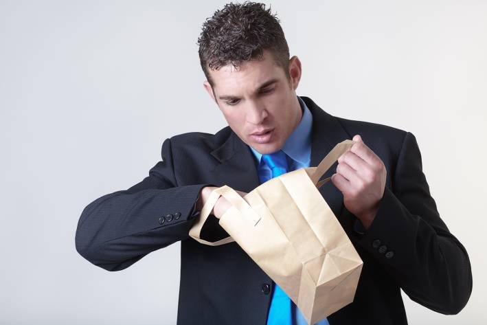 A guy looking in his brown bag lunch at the office