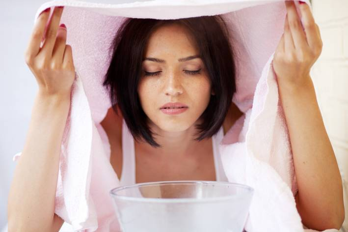 A woman relaxing during a facial steam treatment over a bowl with towel over her head.