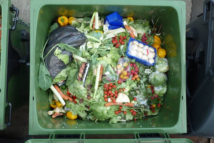 a commercial garbage container full of usable food from the store