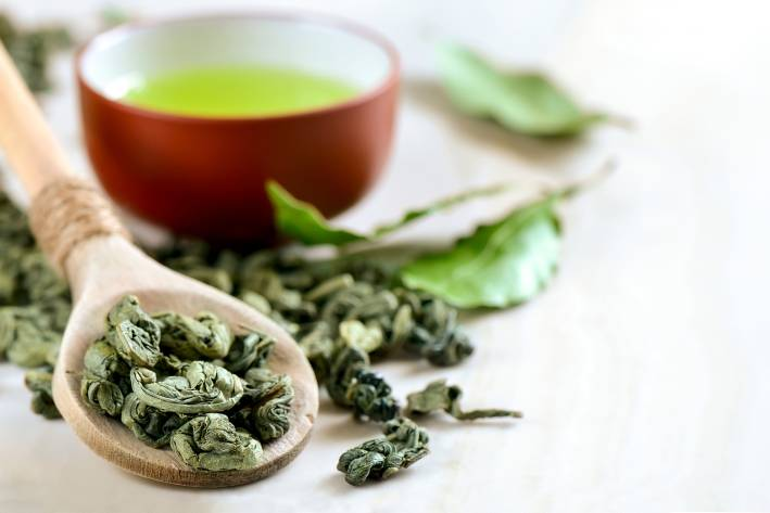 A wooden spoon of dried green tea leaves with a red tea bowl of green tea in the background.