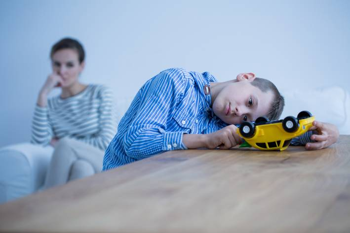 An autistic boy playing with a truck while his mother watches