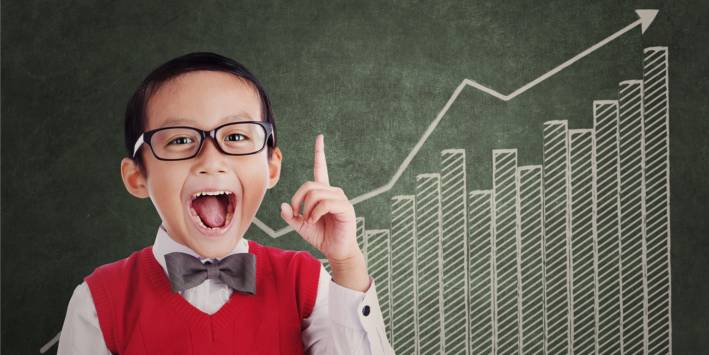 Smart child with glasses in front of chalkboard, arrow pointing up