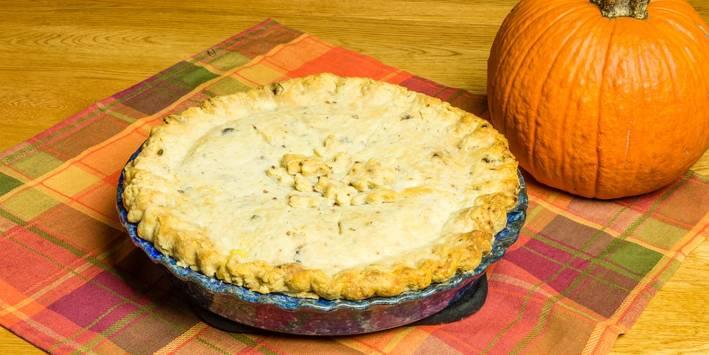 a turkey pot pie next to a pumpkin