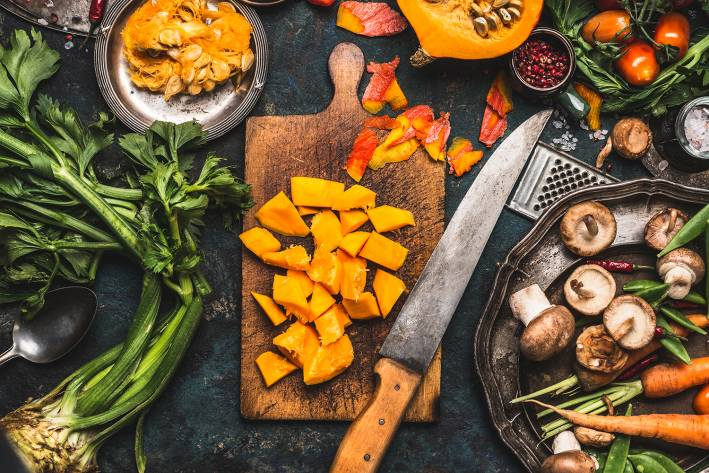 A kitchen knife surrounded by perfectly peeled and cut vegetables and fruit