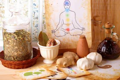 Traditional alternative therapy theme with medicinal herbs and oils with a watercolor of a silhouette of man with chakras in the background.