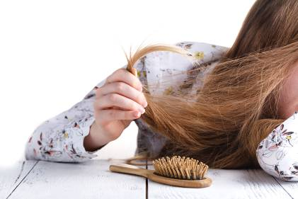A woman holding her hair in her hair to inspect split ends.