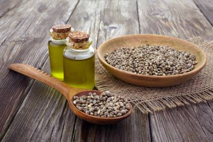 a bowl of hemp seeds and vials of oil