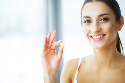 Woman with glowing healthy skin about to take her omega supplement.