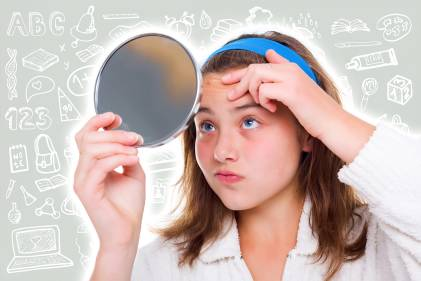A school girl with a mirror, looking at a pimple on her forehead