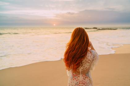 Red head woman on the beach looking at the sea.